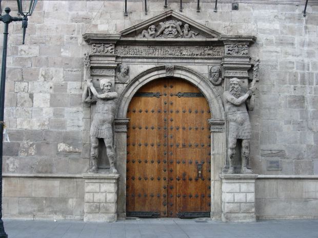 Door of old palace with gatekeeper statue